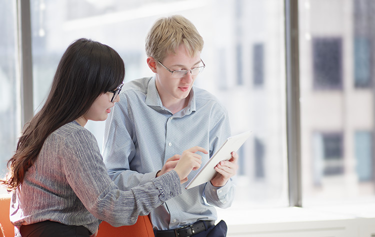 Two young coworkers in discussion while looking at a tablet